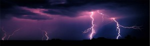 purple sky with lightning striking the ground in the distance